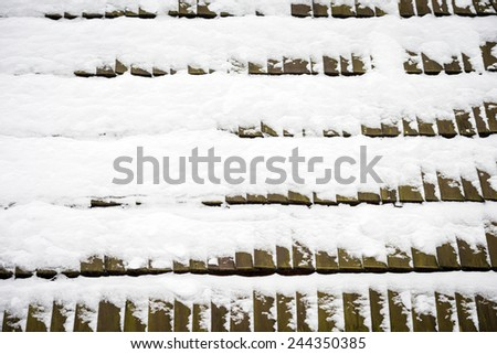 Texture of wooden roof tiles covered with snow - stock photo