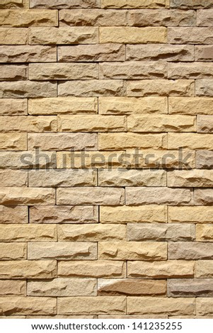 texture of yellow-brown rough brick wall - stock photo