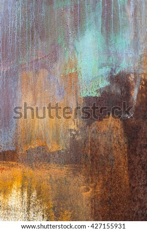 texture peeling metal surface with rust and paint with colored streaks - stock photo