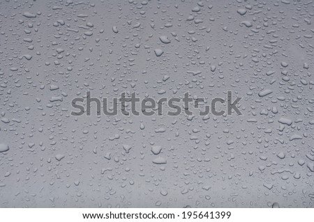 Texture silver hood of the car with raindrops