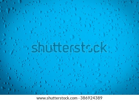 Texture water drops on the blue bottle close-up as a background. - stock photo