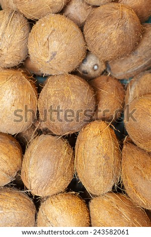 Textured background of stack of hairy brown coconuts - stock photo