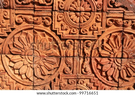 Textured background: traditional handcraft decoration of sunflowers and Wheel of the Law on the brick wall