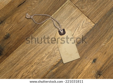 Textured blank tag tied with brown string. Price tag, gift tag, sale tag, address label on wooden floor - stock photo