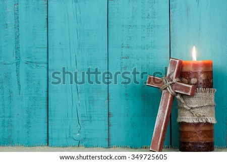 Textured candle burning and rugged wooden cross with rope by antique rustic teal blue wooden background - stock photo