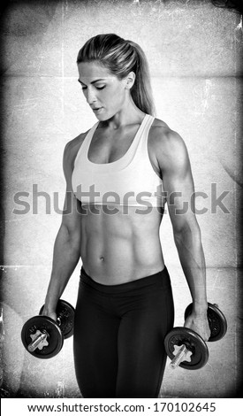 Textured Female Body Builder holding weights - stock photo