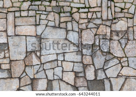 Textured gray wall with cracks and moss