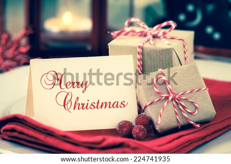 Textured greeting card with copy space for your own text on a plate with wrapped Christmas presents as a concept of a festive dinner with retro vintage filter effect - stock photo