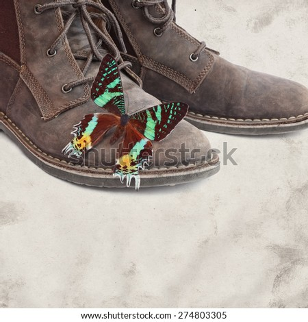 Textured grunge old paper background with boots and butterfly sitting on them. Ecological positive concept - stock photo