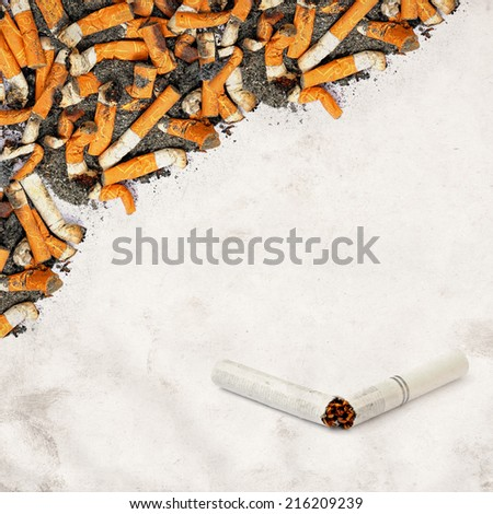 Textured grunge paper background with cigarette butts and broken only cigarette  - stock photo