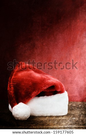 Textured image of a Santa Hat over a rustic wooden background with room for text.
