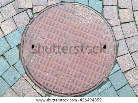 Textured metal manhole cover with holes, closing the technological wells for underground communications. - stock photo