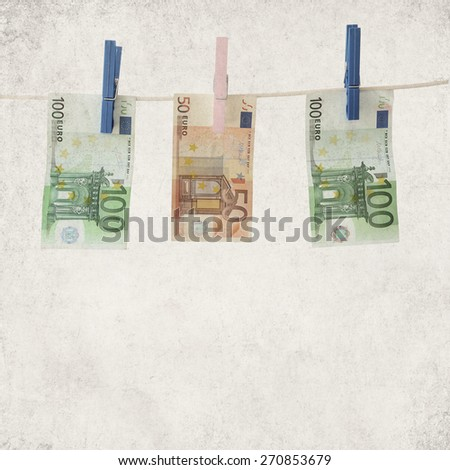 Textured old paper background with banknotes euro on a clothesline - stock photo