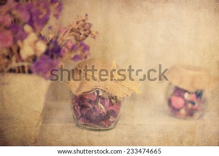 textured old paper background with hibiscus tea in glass jar - stock photo