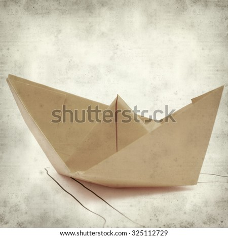 textured old paper background with origami paper boat - stock photo
