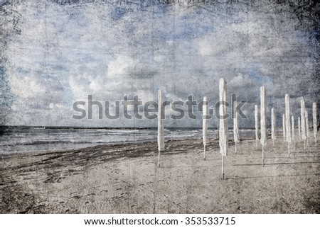 Textured old paper background with winter seascape, sand beach and amazing cloudy sky  - stock photo