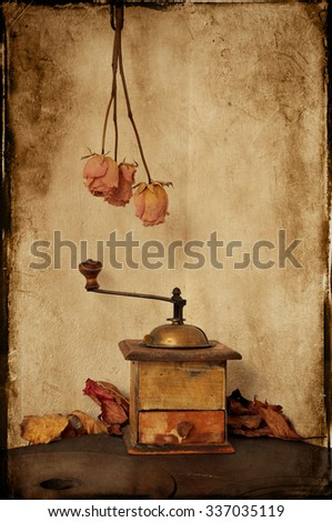 Textured picture of vintage coffee grinder with autumn leaves and dried roses. Grungy style. - stock photo