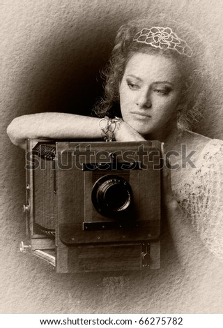 Textured retro photo of young thoughtful woman standing near the outdated camera