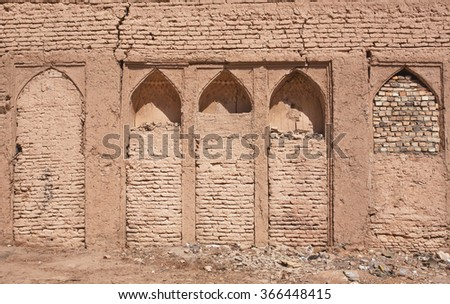 Textured wall with bricked-up niches in an old house of the Middle East - stock photo