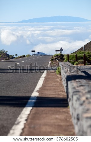 TF-38 route is connecting the Teide volcano and Vilaflor village on Tenerife island. High mountain asphalt road is over clouds - stock photo