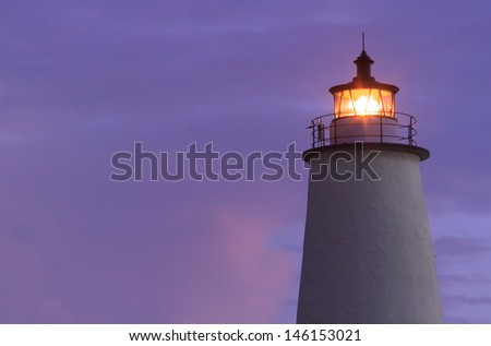 Th Lighthouse on Ocracoke Island shines against a colorful North Carolina sky at dawn. - stock photo