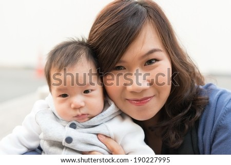 Thai baby male infant with his Thai mother, taken outdoor - stock photo