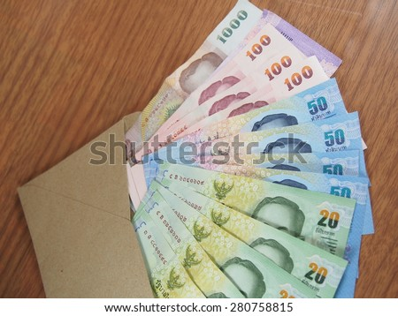 Thai Baht Money, arranged banknotes in brown envelope, soft focus