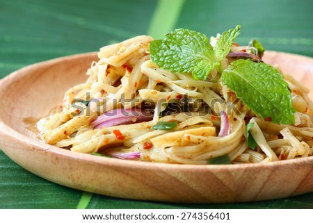 Thai bamboo shoot spicy salad served in wooden plate on banana leaf - stock photo