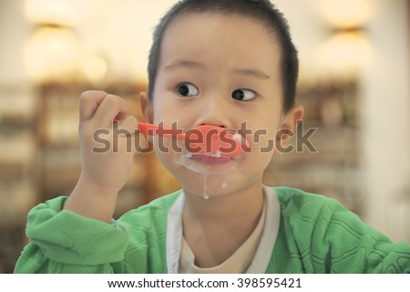 Thai boy eating ice cream with melted part overflow from his mouth to his chin