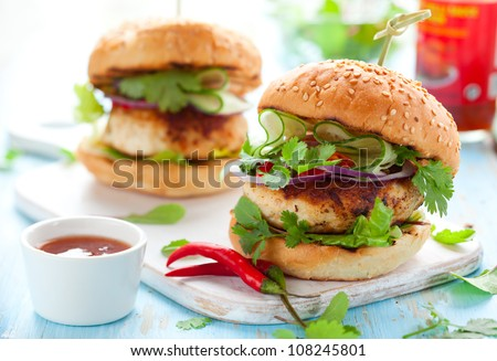 Thai chicken burger with cucumber and sweet chili sauce - stock photo