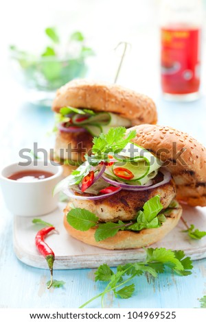 Thai chicken burger with cucumber and sweet chilli sauce - stock photo