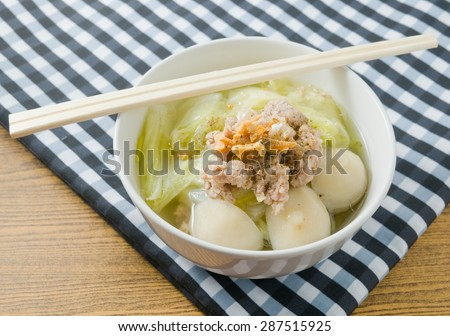 Thai Cuisine and Food, A Bowl of Chinese Cabbage with Minced Pork and Fish Meat Ball Soup Topping with Fried Garlic. - stock photo