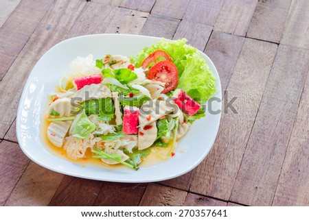 Thai cuisine spicy pork salad on wood background or Yum Moo Yor - stock photo