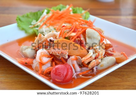 Thai cuisine ,  spicy seafood salad on wooden table