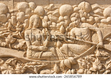 Thai culture stone carving on temple wall - stock photo