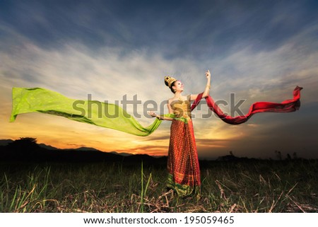 Thai dancing girl with northern style dress in rice field in front off background of sunset - stock photo