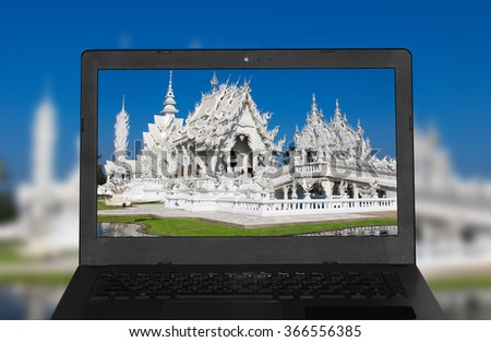 Thai decoration in Wat Rong Kun in Chiang Rai Province Thailand Amazing Wat Thai presented by computer notebook. - stock photo