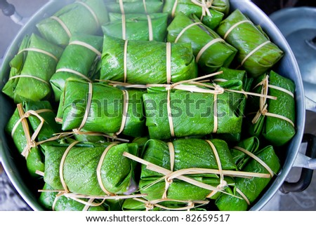 Thai dessert made from rice and banana wrapped in banana leaves. - stock photo