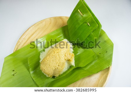 Thai Dessert, sticky rice and egg custard creamy wrapped banana leaf, on a wooden plate,  - stock photo