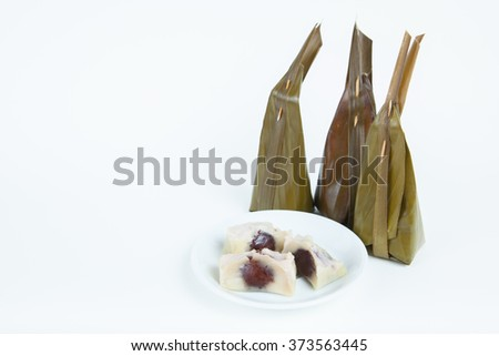 Thai dessert wrapped in banana leaves with long coconut leaves tail on white paper background.
