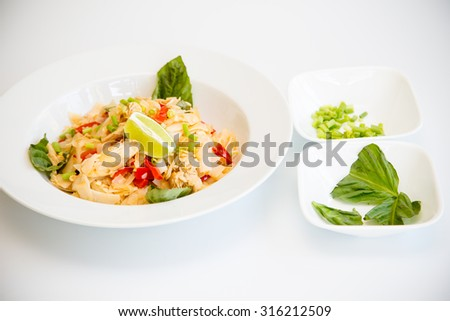 Thai dish of chicken Pad Kee Mao with Bell Pepper and Thai Basil with side garnish of Thai basil, lime, and scallions - stock photo