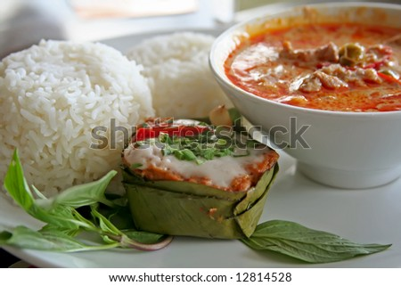 Thai dish of spicy curry steamed fish pudding and rice traditional cuisine - stock photo