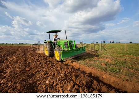 Thai farmer driving tractor plowing the soil for farming - stock photo