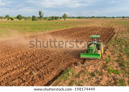 Thai farmer plowing the soil on his tractor - stock photo