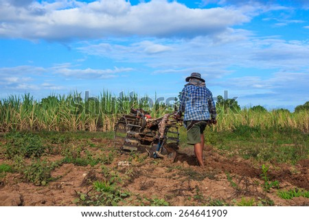 Thai farmer using walking tractors for cultivated soil for prepare plantation. - stock photo