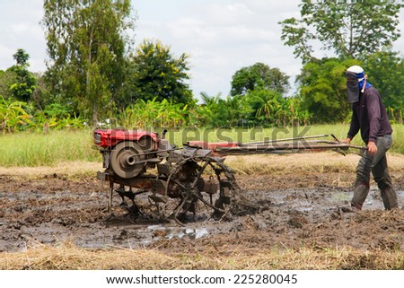 Thai farmer using walking tractors for cultivated soil for rice