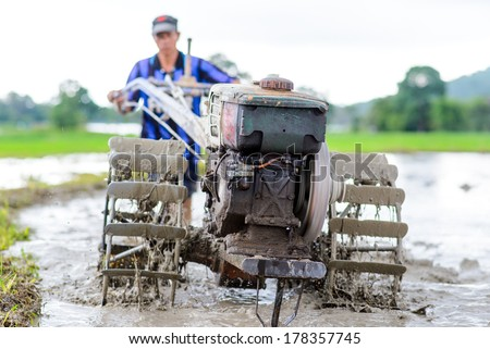 Thai farmer using walking tractors for cultivated soil for rice plantation  - stock photo