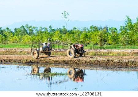 Thai farmer using walking tractors for cultivated soil for rice, Thailand. - stock photo