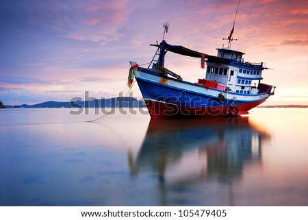 Thai fishing boat used as a vehicle for finding fish in the sea.at sunset - stock photo