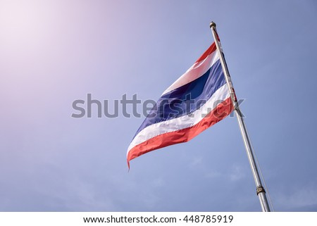 Thai flag on flagpole flying in the wind of Thailand and sun light.